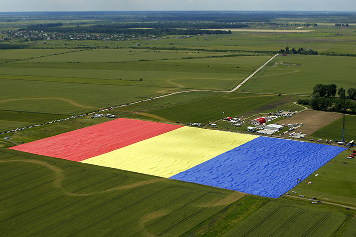 Workers arrange Romania's national flag during a Guinness World Record attempt for the world's biggest national flag in Clinceni